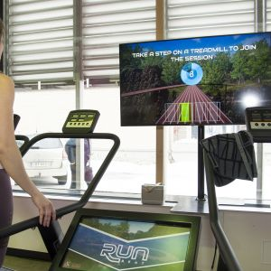 Nainen juoksumatolla edessään näyttö jossa maisema.