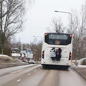 Nuoret roikkuvat linja-auton takapuskurissa.