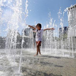 Pikkutyttö leikki suihkulähteessä Adelaidessa keskiviikkona.