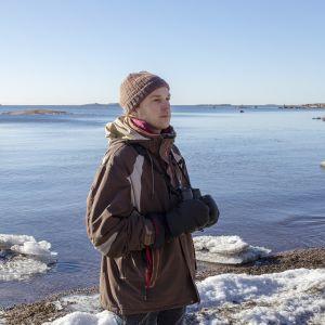 Akatemiatutkija Aleksi Lehikoinen katselee keväistä luontoa Lauttasaaren rannassa Helsingissä.