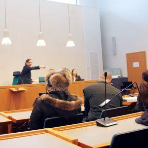 Linja-auton kaappausdraaman oikeuskäsittely Keski-Suomen käräjäoikeudessa. Syytetty istuu karvalakki päässä.