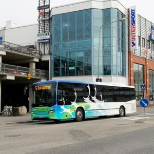 Bussi ajaa kauppakeskuksen edessä Rovaniemellä.