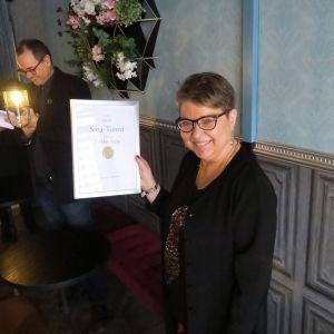 Nainen hymyilee kunniakirja kädessään.
