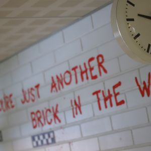 Koulun kello, seinässä teksti All in all you're just another brick in the wall