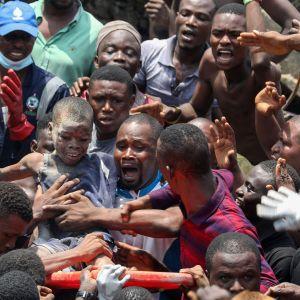 Lasta pelastetaan romahtaneen talon raunioista.