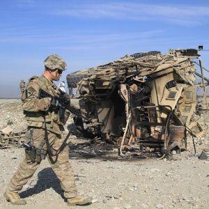 Yhdysvaltalainen sotilas tutkii itsemurhaiskun tuhoamaa ajoneuvoa Afganistanissa.