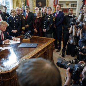 Presidentti Donald Trump allekirjoittaa veto-määräyksen poliisiviranomaisten ympäröimänä.