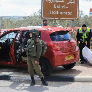 Israelilaiset rikospaikkatutkijat tutkivat autoa jolla surmaaja pakeni.