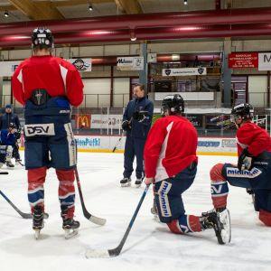 Hermeksen pelaajia kuuntelemassa valmentaja Janne Tuunasen ohjeita.