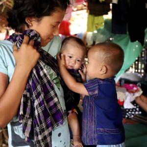 Naisen pitämä pikkuvauva kiinnosti toista lasta väliaikaisella pakolaisleirillä Myitkyinassa Kachinin osavaltiossa toukokuussa 2018. Pakolaisten heikot olot tekevät heistä helposti alttiin saaliin ihmissalakuljettajille.