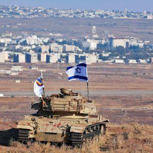 Israelin lippu heiluu vanhassa armeijan tankissa Israelin puolella Golanin kukkuloita.