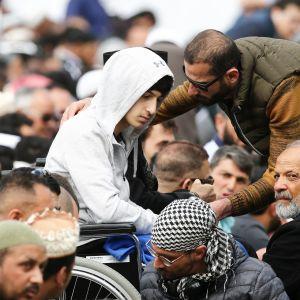 Isänsä ja veljensä viime viikon iskussa menettänyt Zaid Mustafa (keskellä vasemmalla) osallistui rukoushetkeen puistossa al-Noorin moskeijaa vastapäätä Christchurchissa.
