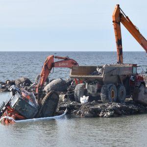 Mereen vajonnut kaivinkone ja muita oransseja työkoneita kapealla aallonmurtajalla, maisema avomerelle.