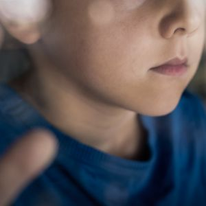 Nuori poika katsoo ikkunasta ulos