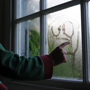 Nuori poikaa piirtää kosteaan ikkunaan surllista naamaa.