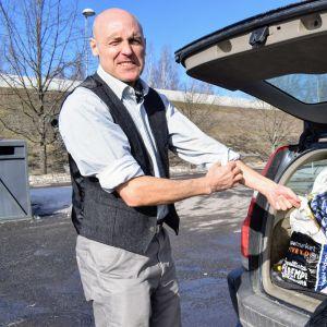 David Stephens käärii hihat, jotta on valmiina hommiin. Vieressä näkyy auton takakontti. joka on täynnä täysinäisiä muovipusseja.