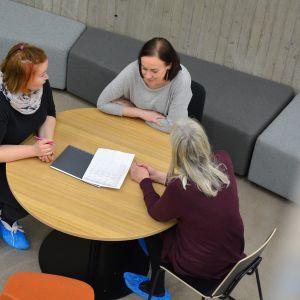 Naiset keskustelevat pöydän ääressä
