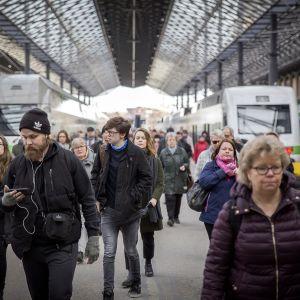 Ihmisiä kävelemässä junilta rautatieasemaa kohti.