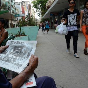 Mies lukee sanomalehteä kadulla Havannassa.