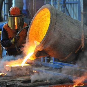 tehdastyöntekijä valuttaa sulaa rautaa