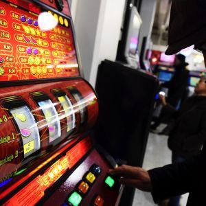 mies pelaa rahapeliä