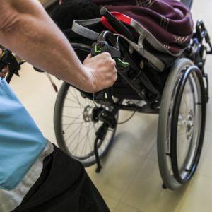 Hoitaja työntää vanhusta pyörätuolissa Tervossa hoivakoti Vuokossa.