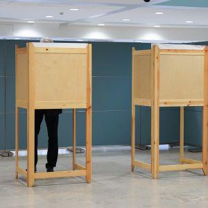 Henkilö äänesti aamupäivällä eduskuntavaaleissa Helsingin kaupungintalolla 14. huhtikuuta.