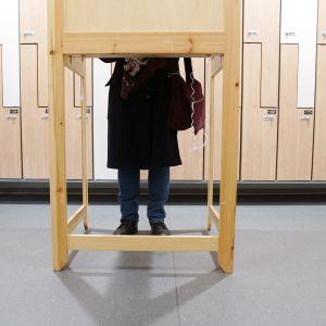 Äänestäjä vaalipaikan äänestyskopissa.