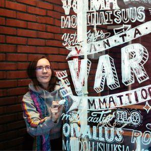 Kuvassa opiskelija kalligrafiatyön vieressä.