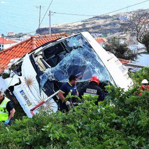 Pelastustyöntekijöitä romuttuneen bussin vierellä.