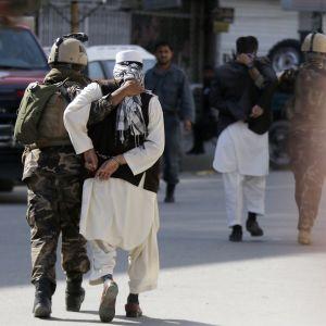 Afganistanin turvajoukkojen sotilas saattoi Kabulissa epäiltyä hyökkääjää pois viestintäministeriön rakennuksesta, jonne oli aiemmin tehty isku.
