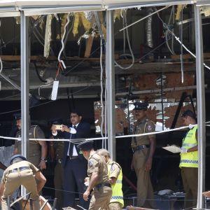 Poliisit käyvät läpi pahoin vaurioitunutta salia. Suurista ikkunoista lasit ovat pudonneet.