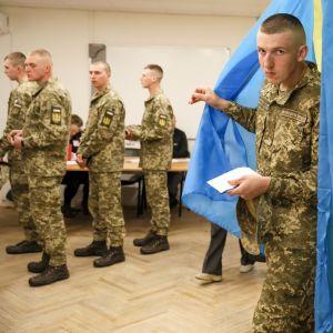 Yksi univormuasuinen nuori mies tulee äänestyskopista, joka on verhottu Ukrainan lipun väreihin. Neljä muuta varusmiestä jonottaa taustalla.