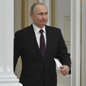 Putin astuu sisään huoneeseen valkoisten pylväiden välistä.
