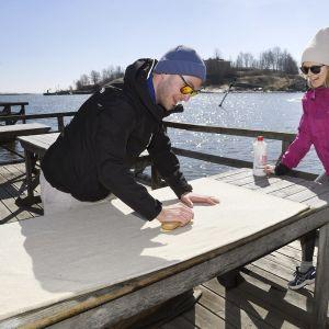 Aki ja Noora Alanne pesevät mattoja Kaivopuiston mattolaiturilla Helsingissä pääsiäissunnuntaina.