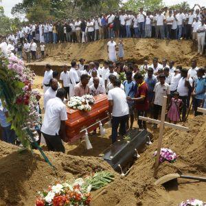 Hautajaisvieraat seuraavat, kun arkkuja lasketaan hautaan.