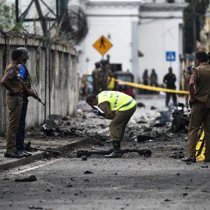 Rikostutkijoita tutkimassa pommin räjähdyspaikkaa.
