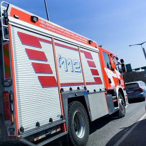 Helsingin kaupungin pelastuslaitoksen paloauto liikennevaloissa.