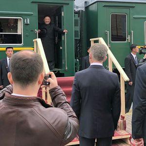 Kim Jong-un seisoo junan oviaukossa. Laiturilla on useita ihmisiä.