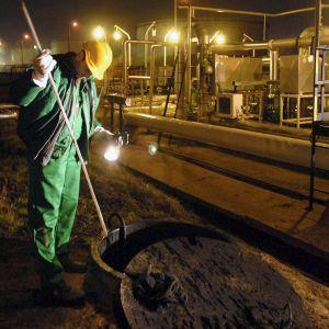 Työntekijä tarkistaa öljyn tason maanalaisesta tankista Szazhalombattassa.