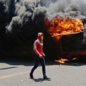 Mielenosoittaja kulkee palavan bussin ohitse Venezuelan Caracasissa.