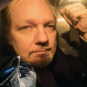 Julian Assange näyttää nyrkkiä kameroille.