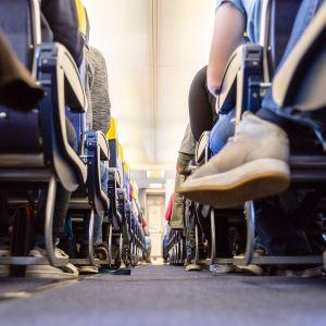 Matkustajien jalkoja lentokoneesa.
