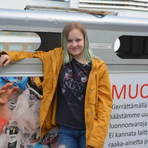 Maija Nisulan käsi komeilee kierrätyskontin kyljessä. Oppilaat ovat osin itse toteuttaneet konttien kuvituksen.
