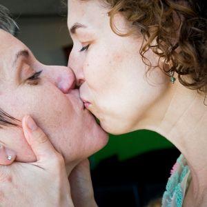 Kaksi naista suutelee.