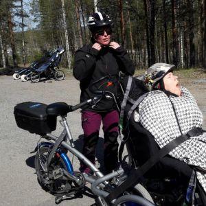 Pyörätuolissa istuva henkilö pääsee polkupyörän kyytiin.