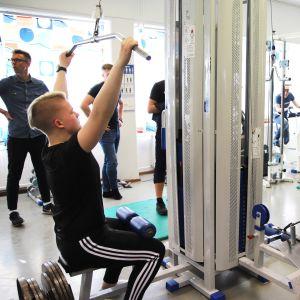 Hepolan koululla personal trainerina työskentelevä Jari Poikela ohjaa nuoria kuntosalilla, kansainväliset vieraat seuraavat kiinnostuneina.