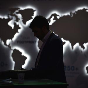 Mies seisoo maailman kartan edessä näkyen vain siluettina.