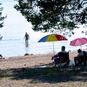 Auringonottajat nauttivat hellepäivästä uimarannalla Oulussa.
