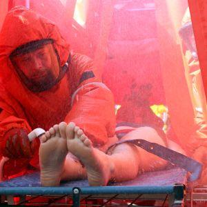 Pelastushenkilöstö pesee kemikaalionnettomuuden uhria teltassa